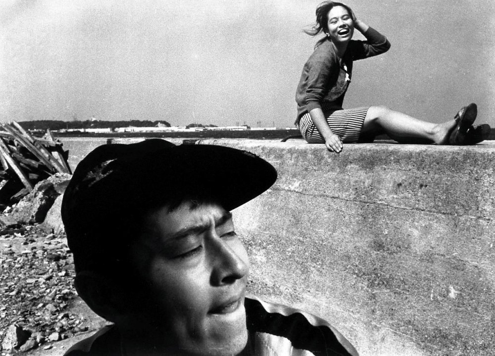 pigs-and-battleships-1961-002-boy-cap-girl-laughing-on-wall
